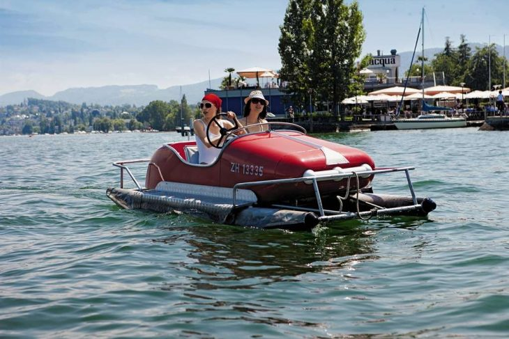 Two women riding a red pedal boat on lake Zurich