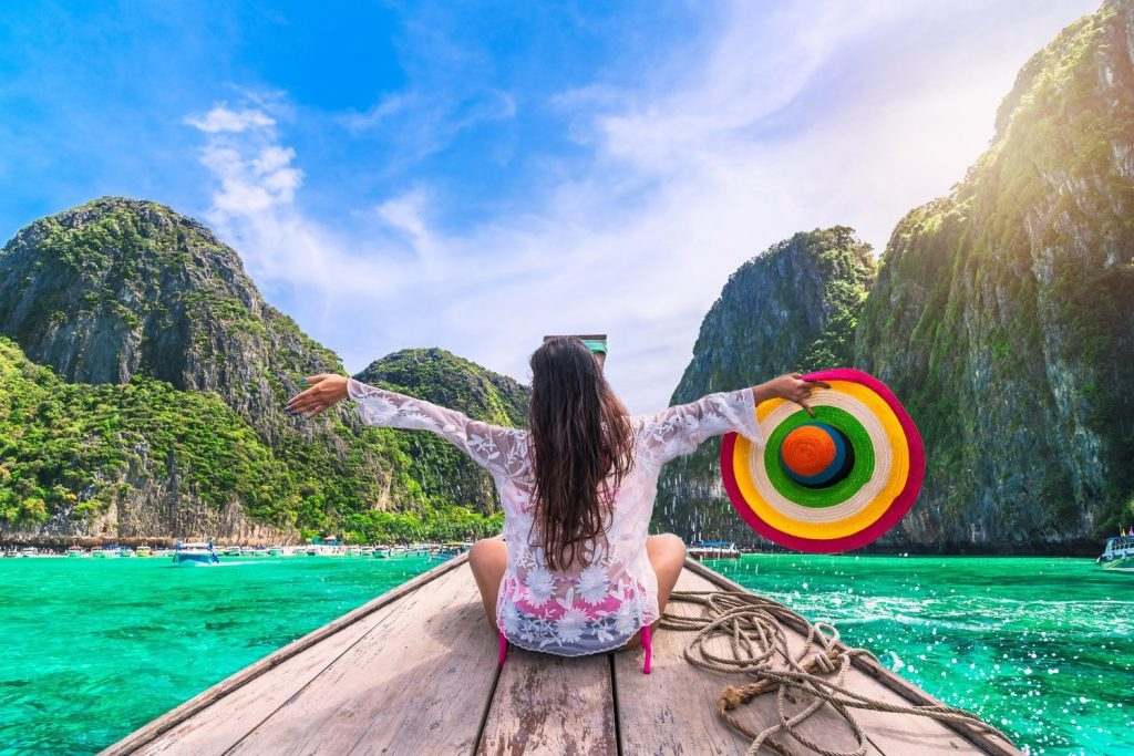 A back view of a woman sitting on a boat and holding a multi-coloured hat on a sea in Thailand